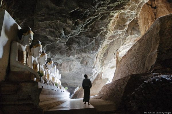 A man walks past Buddha images inside Ya The Byan cave